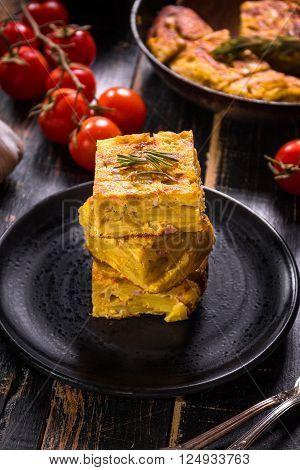 Slice Of Tortilla De Patatas On A Black Plate
