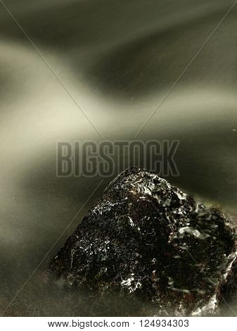 Slippery boulders in mountain stream. Clear water blurred by long exposure, reflection in water level.
