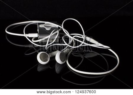 Portable musical player and headphones. isolated on black background