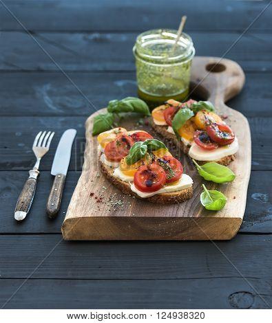 Tomato, mozzarella and basil sandwiches on dark wooden chopping board, pesto jar, dinnerware over black background, selective focus