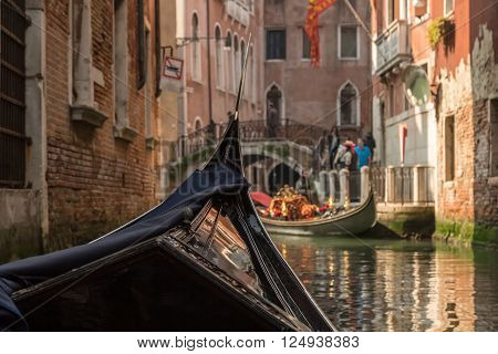 View of a bridge and another gondola shot from within a gondola on a canal in Venice on a bright sunny day showing front of the gondola in the foreground
