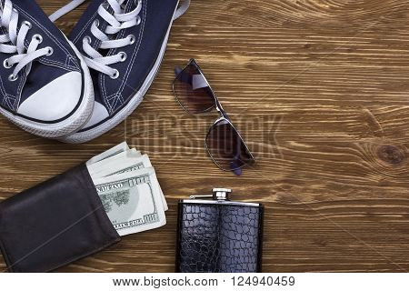 Men's accessories: wallet, sunglasses, flask and  sneakers on wooden background