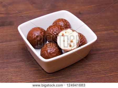 Chocolate pralines on a square bowl on wooden table
