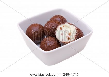 Chocolate pralines on a square bowl on white background