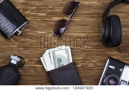 Men's accessories: wallet, headphones, sunglasses, perfume, camera and  flask on wooden background