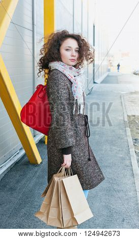 Girl in a coat in the spring, wavy curly hair is developing the wind, full portrait outdoors growth. Happy girl finishes shopping. In the hands packages with purchases. Make purchases with pleasure