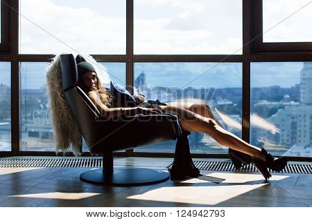 Beautiful girl sitting on a chair her feet up on the window frame in a lace bodysuit, a blue coat and wearing shoes with heels can be seen outside the city. On a chair thrown over the white skin