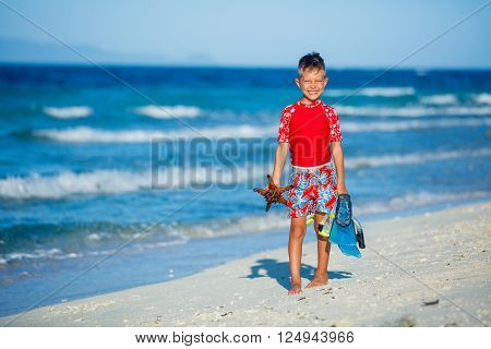 Joyful boy on the tropical beach with equipment to scuba diving and starfish.