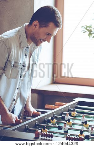 One more goal. Side view of cheerful young handsome man playing foosball game and looking excited while standing in front of window