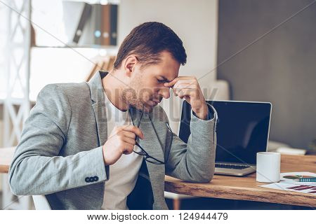 Feeling tired. Frustrated young handsome man looking exhausted while sitting at his working place and carrying his glasses in hand