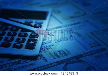 Pencil and calculator on dollar bank note money Blue tone Finance concept