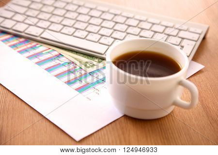 Laptop with stack of folders on table on white background.