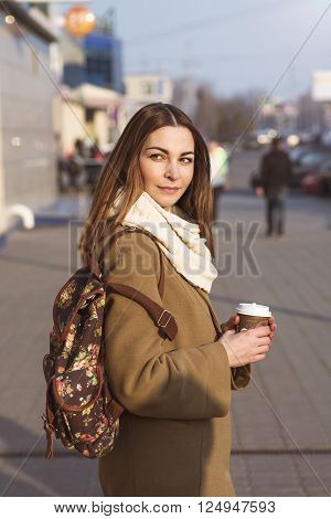 Portrait of a beautiful young brunette woman looking into the distance, in a coat and a scarf, standing in the street in spring or autumn. In her hand a cup of hot tea or coffee, fashion shoulder bag.