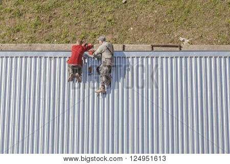 Szczecin Poland - April 07 2016: Workers repairing a store roof made of corrugated metal sheets picture taken from above.