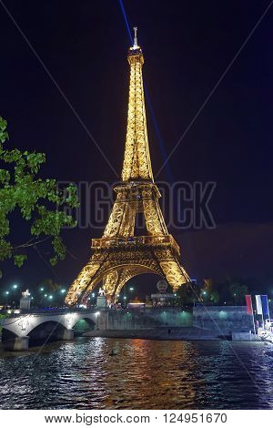 paris france - may 3 2012: illuminated eiffel tower and seine river in paris in france in the evening. eiffel tower is an iron lattice tower of paris. it is a global and cultural icon for france