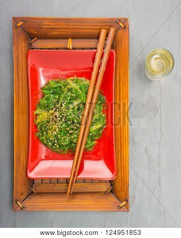 Fresh seaweed salad on a red plate with chopsticks.