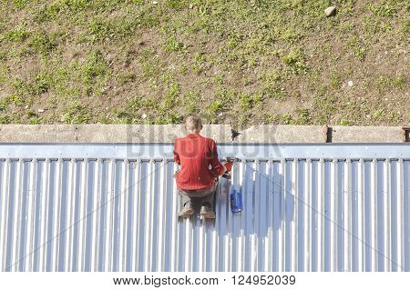 Szczecin, Poland - April 07, 2016: Man with a drill reparing a store roof made of corrugated metal sheets, picture taken from above.