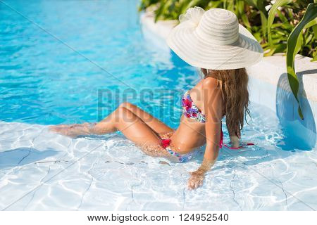 Girl in the swimming pool in the white hat
