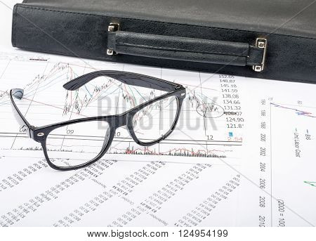 Glasses and suitcase on grpahical charts background, business concept