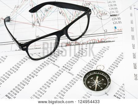 Glasses and compass on grpahical charts background, business concept