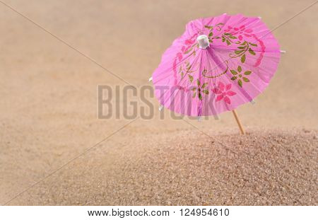 Cocktail Umbrella Close-up In A Sand