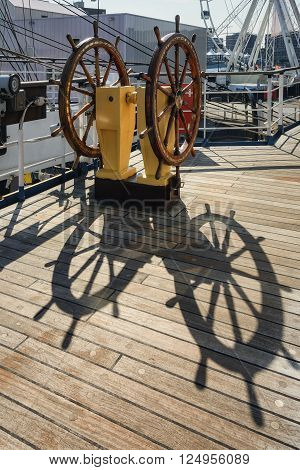 Steering wheel of the ship and its shadow on the deck.