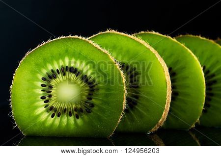 four cut slices of kiwi fruit on black background horizontal. space for text