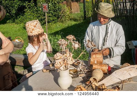 Suzdal, Russia - August 29, 2009: The elderly master in production of birch bark products with the granddaughter shows goods in the museum of wooden architecture