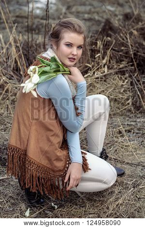 Girl in fashionable clothes sitting against a background of dry branches and holding a wilted bouquet