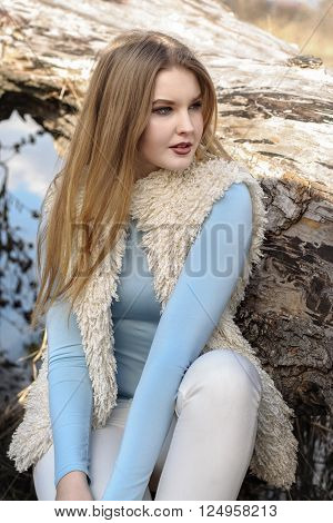 Blonde girl in fashionable clothes posing against the backdrop of driftwood