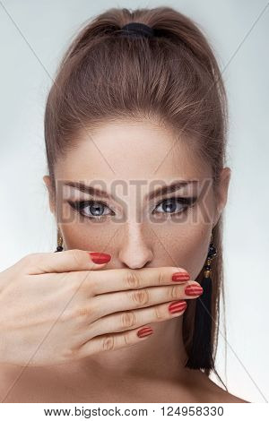 Bright beautiful girl covers her mouth with her hands and is silent