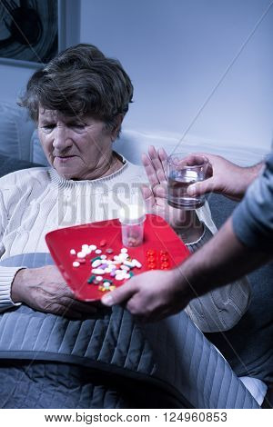 Picture of an old woman refusing to take her medication