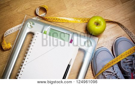 Sneakers centimeter green apple notebook scale. Weight loss healthy lifestyle concept
