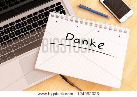 Danke - german word for thank you - handwritten text in a notebook on a desk - 3d render illustration.