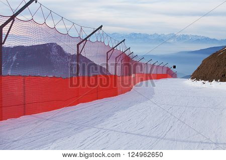 Skiing slope bordered with red net, Dolomites, Italy