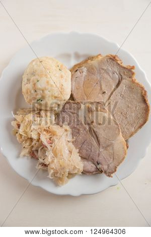 Roasted Pork with dumplings and cabbage on a plate