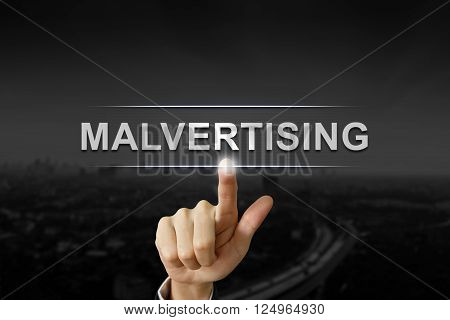 business hand clicking malvertising button on black blurred background
