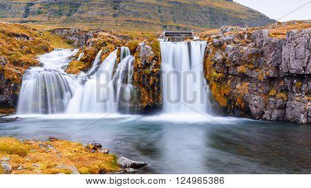 Beautiful waterfall landscape at Kirkjufell mountain Snaefellsnes peninsula Iceland hot summer tone