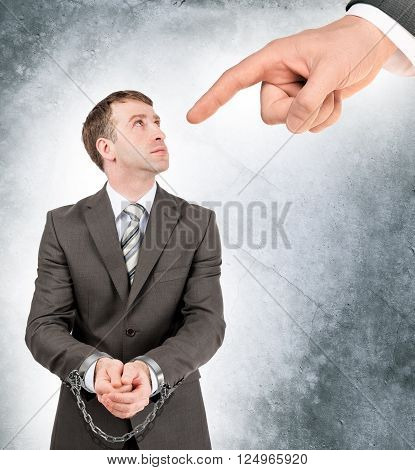 Businessman in cuffs with chain looking on big hand pointing at him on grey wall background