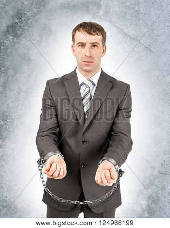 Angry businessman in cuffs on grey wall background
