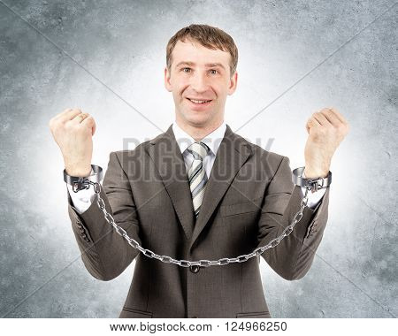 Happy businessman in cuffs looking at camera on grey wall background