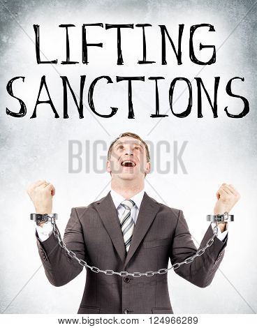Happy businessman in cuffs looking at lifting sanctions on grey wall background