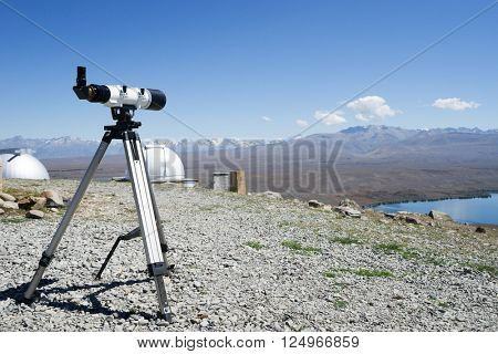 telescope and observatory on ground near lake in summer day in new zealand