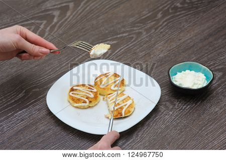 Girl eats cottage cheese pancakes homemade traditional Ukrainian and Russian syrniki. Woman with piece of mini pancake knife and fork in arms. Brown a wooden background.