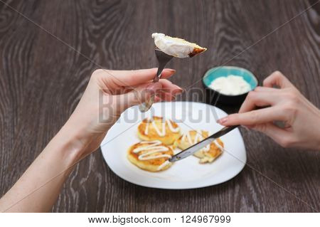 Girl eats cottage cheese pancakes homemade traditional Ukrainian and Russian syrniki. Woman with piece of mini pancake knife and fork in arms. Watching a person eat. Brown a wooden background.