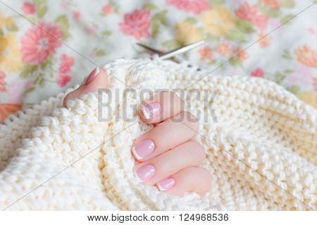 Little female hand with manicure holds connected to the spokes of a soft beige sweater yarn.