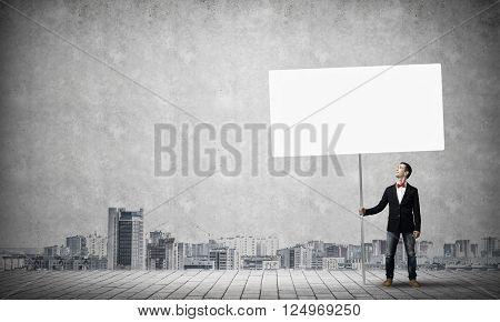 Fullbody of handsome guy holding white blank banner