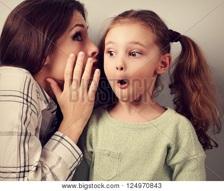 Shocked Mother Whispering The Secret Information To Her Surprising Cute Girl In Ear On Blue Backgrou