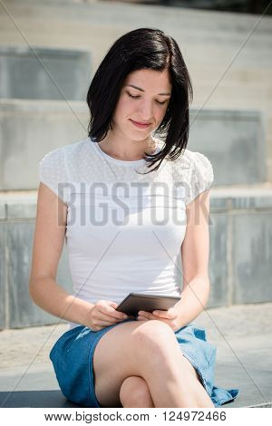 Young woman reading book on electronic book-reader in urban environment