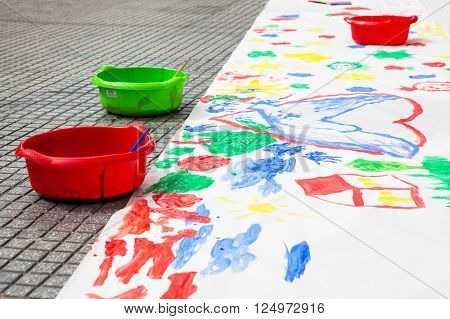 Child paintings and three bowls with  paint on flour
